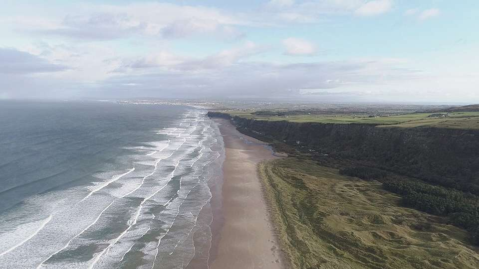Benone Beach looking toward Mussden Temple.  Blue skies, sandy beach and waves are rolling in.